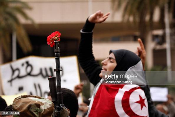 Demonstrators place flowers in the barrels of soldiers guns as people take to the streets again to protest for changes in Tunisia's new government on...