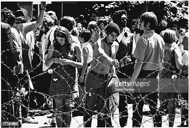 Demonstrators place flowers on a barbed wire fence in People's Park on the campus of the University of Berkeley California May 30 1969 The...