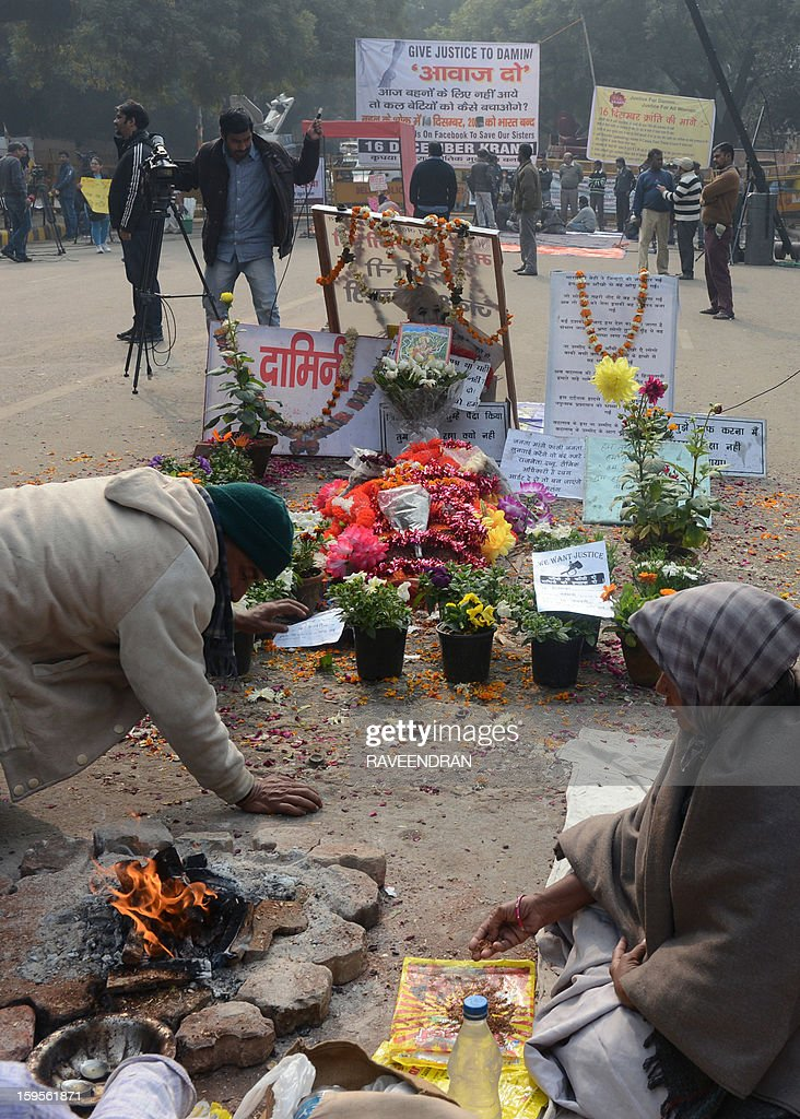 Demonstrators pray at a memorial during the one-month anniversary of the gang rape and murder of a student in New Delhi on January 16, 2013. Indian prosecutors said that the five adults charged with the murder and gang-rape of a student in New Delhi are 'dangerous men' and should be handcuffed while in custody.