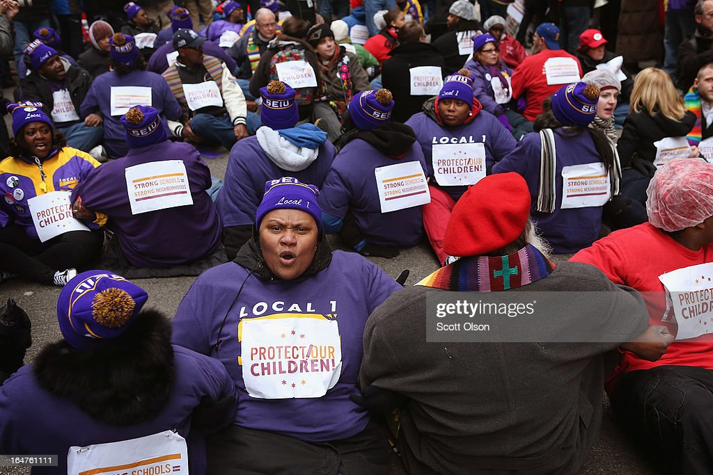 Demonstrators prepare to be arrested while protesting school closings on March 27, 2013 in Chicago, Illinois. More than 1,000 demonstrators held a rally and marched through downtown to protest a plan by the city to close more than 50 elementary schools, claiming it is necessary to rein in a looming $1 billion budget deficit. The closings would shift about 30,000 students to new schools and leave more than 1,000 teachers with uncertain futures.