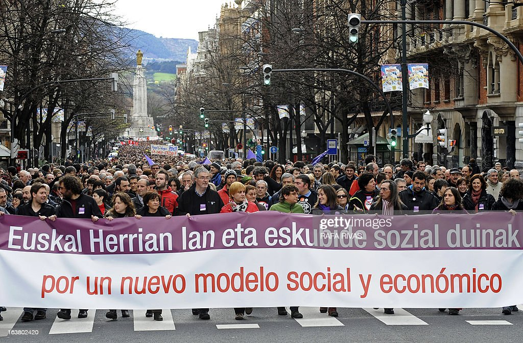 Demonstrators protest against Spanish government's austerity measures during a demonstration called by several Basque unions and social collectives in the Northern Spanish Basque city of Bilbao on March 16, 2013. The banner reads in Basque and Spanish 'Decent jobs and social rights in the Basque Country. In favour of a new social and economic model'.