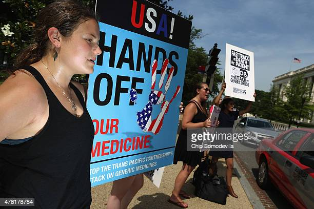 Demonstrators protest against the Trans Pacific Partnership trade agreement outside the Senate office buildings on Capitol Hill June 23 2015 in...