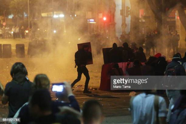 Demonstrators protest amidst tear gas during an antiTemer protest on May 18 2017 in Rio de Janeiro Brazil Thousands of protestors hit the streets of...