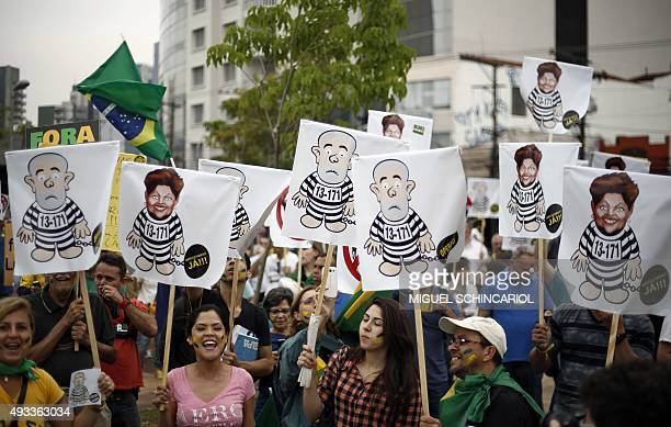 Demonstrators protest for Brazilian President Dilma Rousseff's impeachment with signs depicting her and former Brazilian president Luiz Inacio Lula...