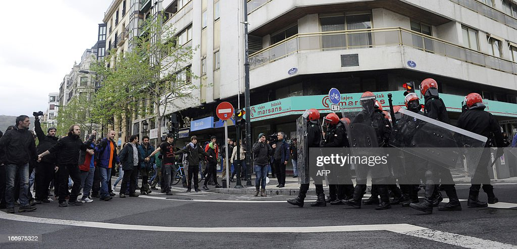 Demonstrators (L) protest in front of members of the Ertzaintza Basque Police (R) after six members of the Basque pro-independence youth organization SEGI were arrested in the northern Spanish Basque city of San Sebastian on April 19, 2013. Hundreds of people have remained gathered in San Sebastian during two days to try to prevent the incarceration of eight members of SEGI sentenced to six years in prison by the Supreme Court. The Spanish Court issued arrest warrants on April 16 against Mikel Arretxe, Imanol Vicente, Naikari Otaegi, Egoi Alberdi, Aitor Olaizola, Adur Fernandez, Oier Lorente y Ekaitz Ezkerra for membership in an organized armed group.