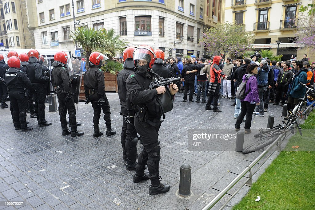 Demonstrators (R) protest in front of members of the Ertzaintza Basque Police (L) after six members of the Basque pro-independence youth organization SEGI were arrested in the northern Spanish Basque city of San Sebastian on April 19, 2013. Hundreds of people have remained gathered in San Sebastian during two days to try to prevent the incarceration of eight members of SEGI sentenced to six years in prison by the Supreme Court. The Spanish Court issued arrest warrants on April 16 against Mikel Arretxe, Imanol Vicente, Naikari Otaegi, Egoi Alberdi, Aitor Olaizola, Adur Fernandez, Oier Lorente y Ekaitz Ezkerra for membership in an organized armed group.