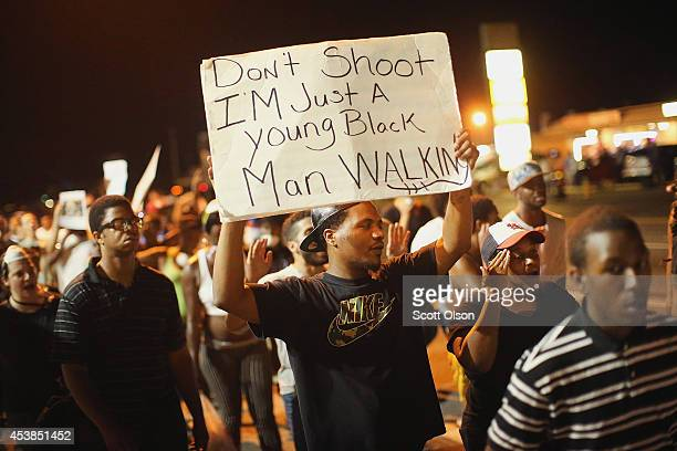 Demonstrators protest the killing of teenager Michael Brown on August 19 2014 in Ferguson Missouri Brown was shot and killed by a Ferguson police...