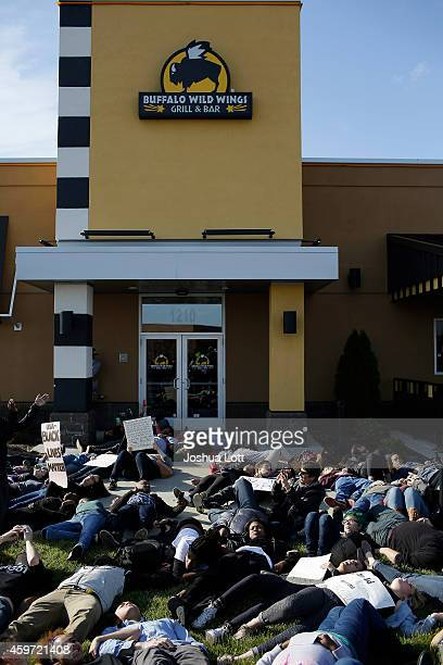 Demonstrators protest the shooting death of Michael Brown stand outside Buffalo Wild Wings during a die in November 29 2014 in Brentwood Missouri...