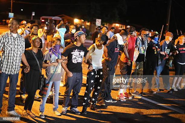 Demonstrators protest the shooting death of teenager Michael Brown on August 13 2014 in Ferguson Missouri Brown was shot and killed by a Ferguson...