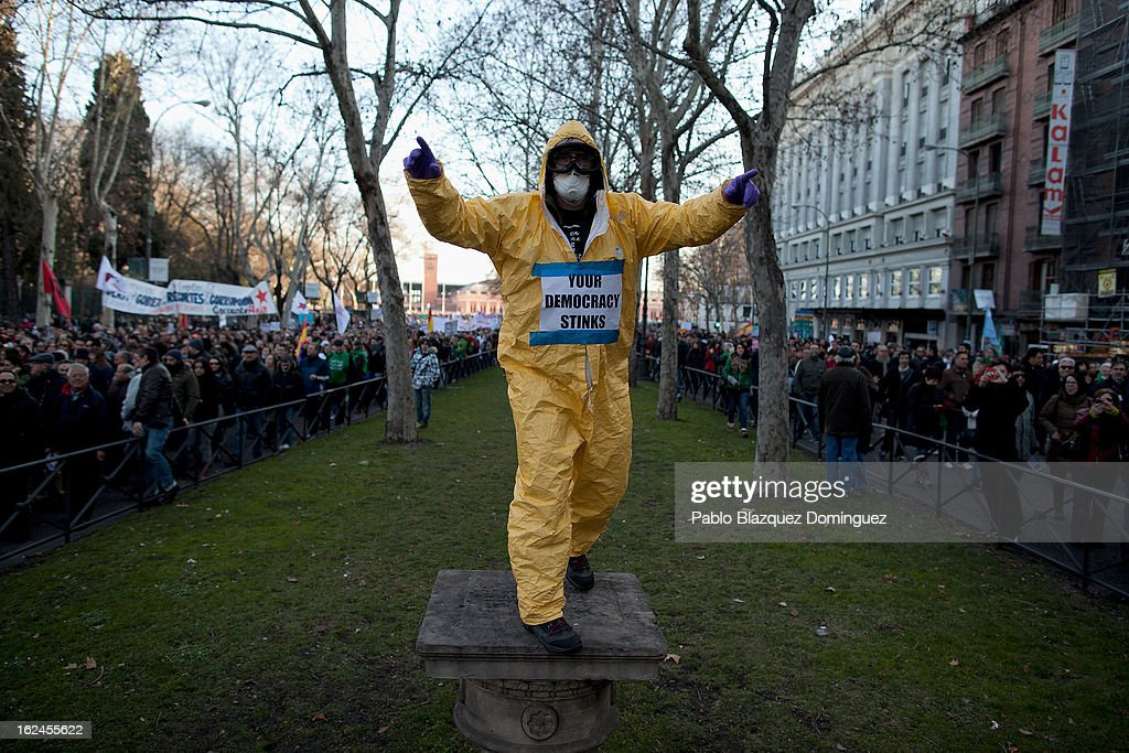 A demonstrators protest wearing a placards reading 'Your democrazy stinks' during a march by thousands of people on February 23, 2013 in Madrid, Spain. Public health workers, civil servants and disaffected citizens converged on central Madrid to protest against the austerity measures of Prime Minister Mariano Rajoy.