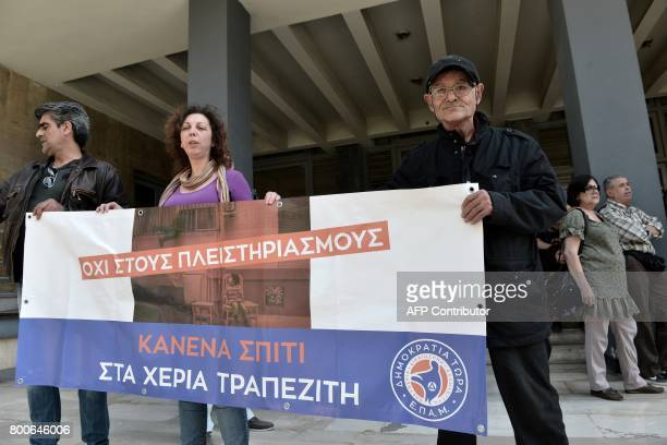 Demonstrators protesting against real estate auctions hold a banner reading ''Not a single home in bankers' hands' in front of Thessaloniki's...