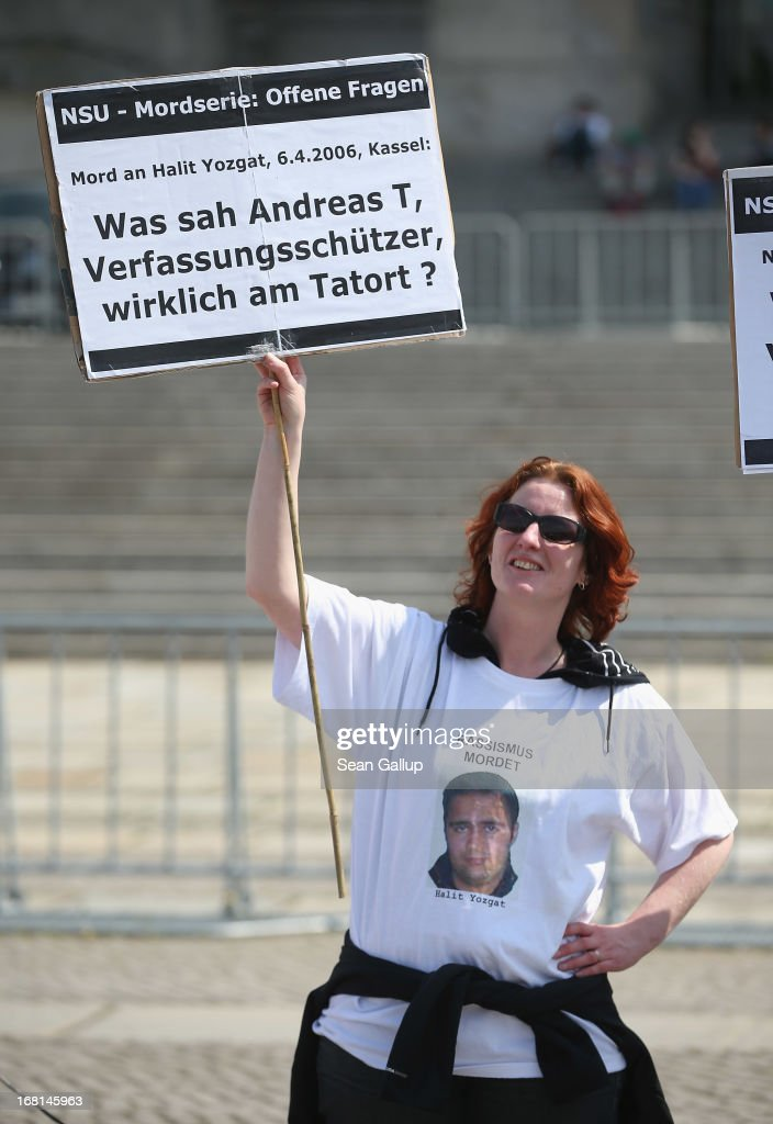 Demonstrators protesting against right-wing violence, including one woman holding a sign that reads: 'What did Andreas T., an agent of the Office for the Protection of the Consitution, really see at the crime scene?' on the first day of the NSU neo-Nazi murder trial on May 6, 2013 in Berlin, Germany. Andreas T., who works for Germany's anti-terrorism agency, the Office for the Protection of the Consitution, was at the Internet cafe in Kassel when NSU members murdered Halit Yozgat in 2006, though T. claims to have seen nothing relevant to the crime. The main defendant in the trial, which began today in Munich, Beate Zschaepe, is on trial for her role in assisting Uwe Boehnhardt and Uwe Mundlos in the murder of nine immigrants and one policewoman across Germany between 2000 and 2007, and four other co-defendants, including Ralf Wohlleben, Holder G., Carsten S. and Andre E., are accused of assisting the trio. Zschaepe, Mundlos and Boehnhardt lived together for years undetected by police and called themselves the National Socialist Underground, or NSU. The case only came to light after Mundlos and Boehnhardt committed suicide after the two were cornered by police following a bank robbery in 2011.