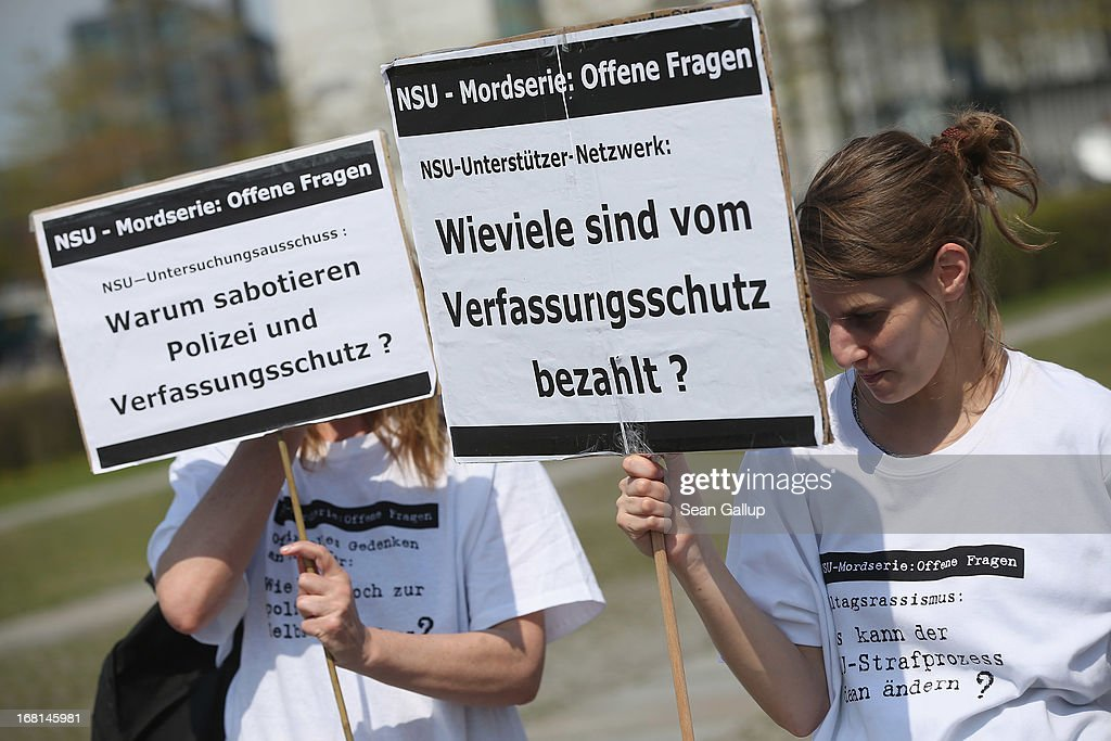 Demonstrators protesting against right-wing violence, including two with signs that read: 'NSU Investigation Commission: Why Are Police and the Office for the Protection of the Constitution Sabotaging?' and 'NSU Supporters' Network: How Many Are Paid by the Office for the Protection of the Constitution?'' on the first day of the NSU neo-Nazi murder trial on May 6, 2013 in Berlin, Germany. The main defendant in the trial, which began today in Munich, Beate Zschaepe, is on trial for her role in assisting Uwe Boehnhardt and Uwe Mundlos in the murder of nine immigrants and one policewoman across Germany between 2000 and 2007, and four other co-defendants, including Ralf Wohlleben, Holder G., Carsten S. and Andre E., are accused of assisting the trio. Zschaepe, Mundlos and Boehnhardt lived together for years undetected by police and called themselves the National Socialist Underground, or NSU. The case only came to light after Mundlos and Boehnhardt committed suicide after the two were cornered by police following a bank robbery in 2011.