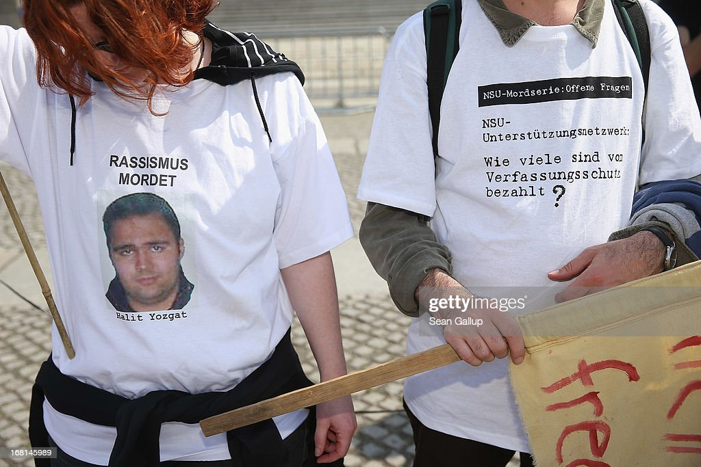 Demonstrators protesting against right-wing violence, including two wearing t-shirts that read: 'Racism Murders - Halit Yozgat' and 'NSU Supporters' Network: How Many Are Paid by the Office for the Protection of the Constitution?'' on the first day of the NSU neo-Nazi murder trial on May 6, 2013 in Berlin, Germany. The main defendant in the trial, which began today in Munich, Beate Zschaepe, is on trial for her role in assisting Uwe Boehnhardt and Uwe Mundlos in the murder of nine immigrants and one policewoman across Germany between 2000 and 2007, and four other co-defendants, including Ralf Wohlleben, Holder G., Carsten S. and Andre E., are accused of assisting the trio. Zschaepe, Mundlos and Boehnhardt lived together for years undetected by police and called themselves the National Socialist Underground, or NSU. The case only came to light after Mundlos and Boehnhardt committed suicide after the two were cornered by police following a bank robbery in 2011.
