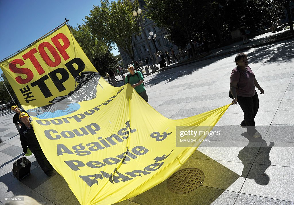 Demonstrators protesting against the Trans-Pacific Partnership (TPP) are seen on Pennsylvania Avenue, near the White House, on September 24, 2013 in Washington, DC. The TPP is a proposed free trade agreement being negotiated by Australia, Brunei, Canada, Chile, Japan, Malaysia, Mexico, New Zealand, Peru, Singapore, the United States and Vietnam. AFP PHOTO/Mandel NGAN