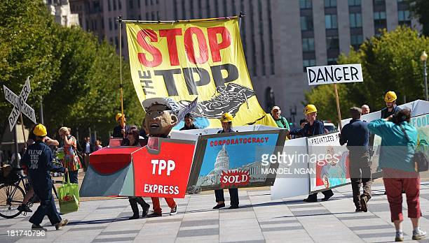 Demonstrators protesting against the TransPacific Partnership are seen on Pennsylvania Avenue near the White House on September 24 2013 in Washington...