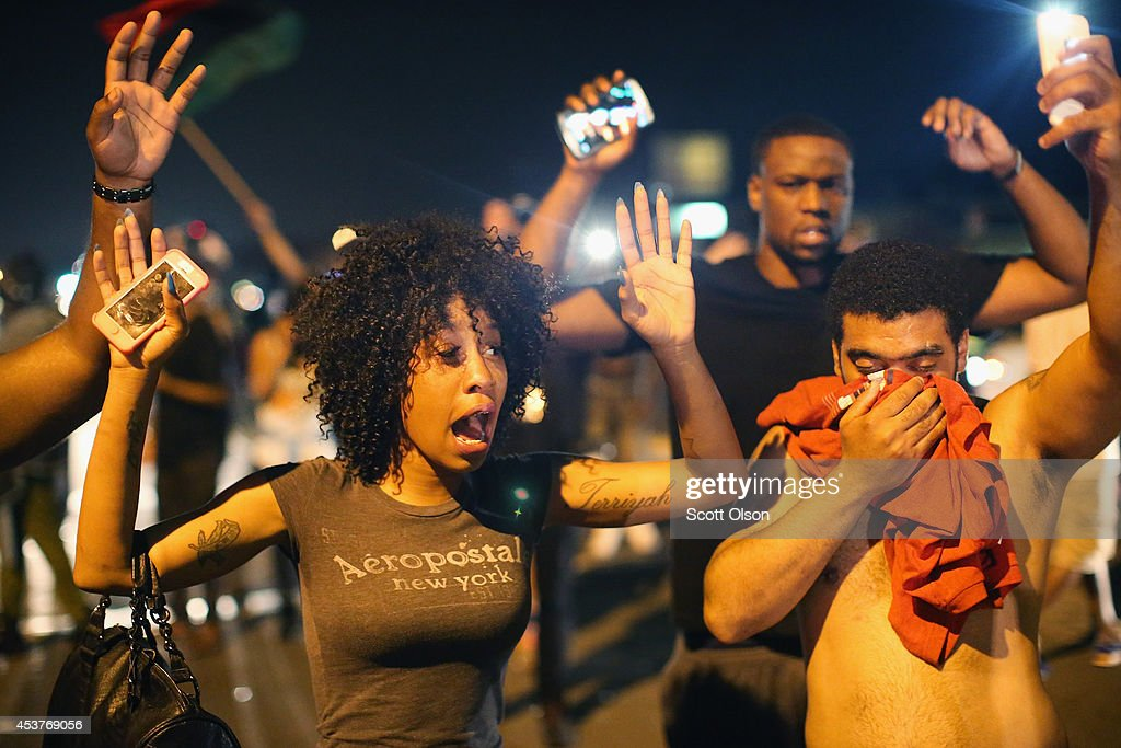 Demonstrators protesting the killing of teenager Michael Brown by a Ferguson police officer try to stand their ground despite being overcome by tear gas on August 17, 2014 in Ferguson, Missouri. Despite the Brown family's continued call for peaceful demonstrations, violent protests have erupted nearly every night in Ferguson since his death.