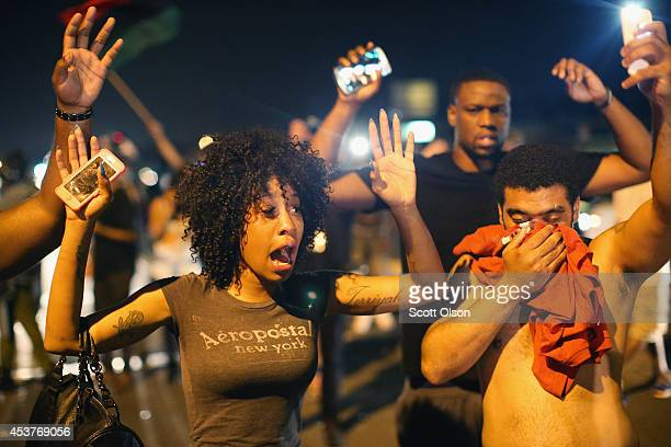 Demonstrators protesting the killing of teenager Michael Brown by a Ferguson police officer try to stand their ground despite being overcome by tear...