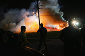 Demonstrators protesting the shooting death of teenager Michael Brown scramble for cover as police fire tear gas on August 13 2014 in Ferguson...
