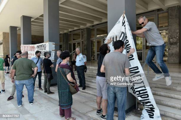Demonstrators put banners outside Thessaloniki's courthouse as they protest against real estate auctions on June 21 2017 A tacit ban on thousands of...