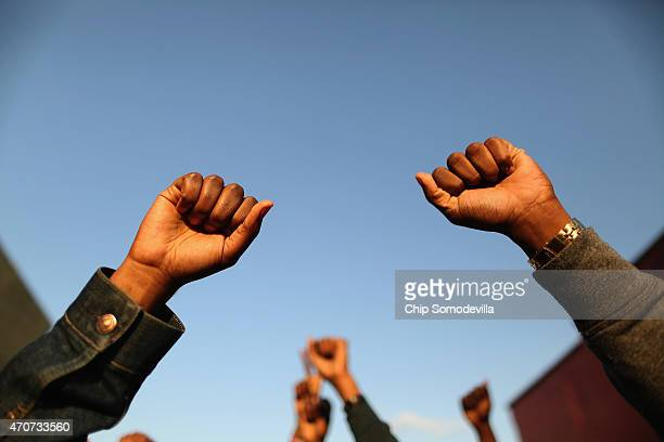 Demonstrators put their fists in the air as a sign of 'black power' during a protest against police brutality and the death of Freddie Gray outside...