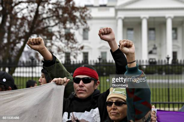 Demonstrators raise their fists in front of the White House during a protest against the Dakota Access Pipeline in Washington DC US on Friday March...