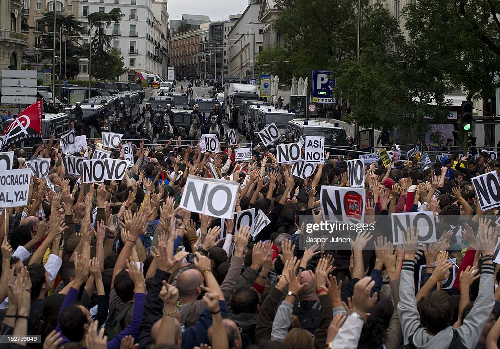Demonstrators raise their hands in protest, while riot policemen wait at the other side of a fence blocking the acces to the Spanish parliament, just before clashing during a protest against spending cuts and the government of Mariano Rajoy on September 25, 2012 in Madrid, Spain. Demonstrators from various organizations, demanding a new constitutional process, are marching today from three different locations in the center of Madrid to the lower house in the Spanish parliament.