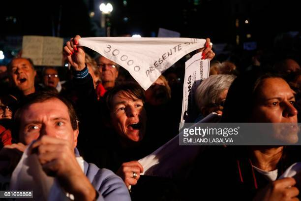 Demonstrators raise white headscarves that the Mothers and Grandmothers of the Plaza de Mayo wear to symbolize the diapers once used by their...