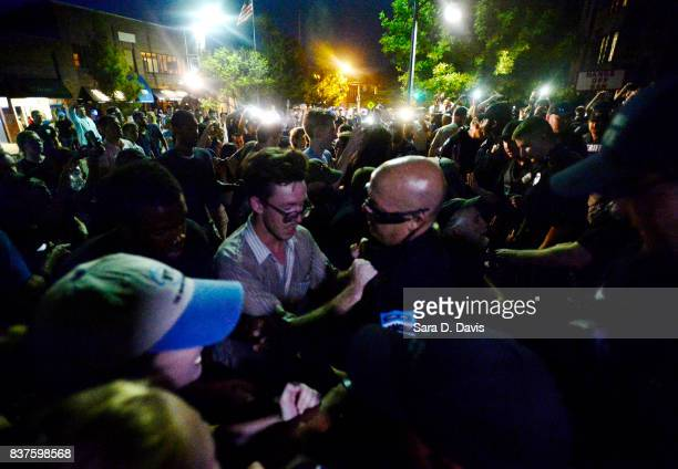 Demonstrators rallying for the removal of a Confederate statue coined Silent Sam on the campus of the University of Chapel Hill are shoved into the...