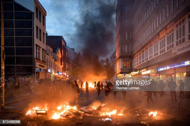 Demonstrators react next to a burning crush barrier during a demonstration against the G20 Summit on July 7 2017 in Hamburg Germany Leaders of the...