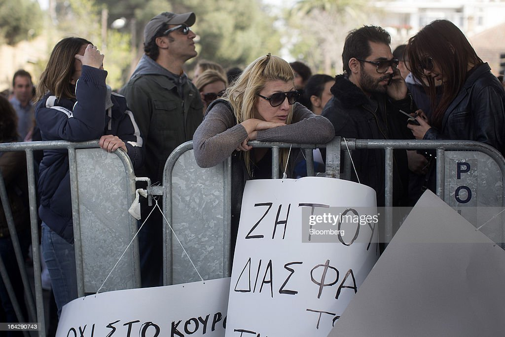 Demonstrators react while standing behind a security cordon during a protest outside the Cypriot parliament in Nicosia, Cyprus, on Friday, March 22, 2013. The aid package Cyprus is seeking would only provide temporary relief as it risks triggering a capital flight that would push the nation closer to needing to restructure its debts. Photographer: Simon Dawson/Bloomberg via Getty Images