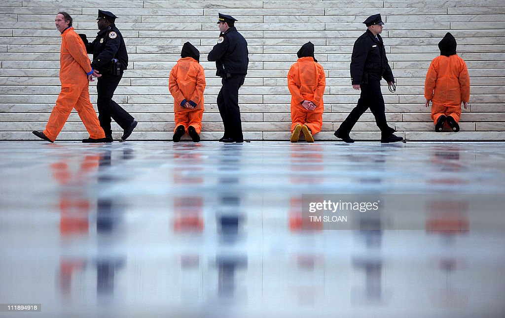 Demonstrators representing prisoners at the US Guantanamo Bay Naval Base are arrested on the US Supreme Court steps during a rally against torture sponsored by Witness Against Torture with Amnesty International and the National Religious Campaign Against Torture 11 January, 2008 in Washington, DC.