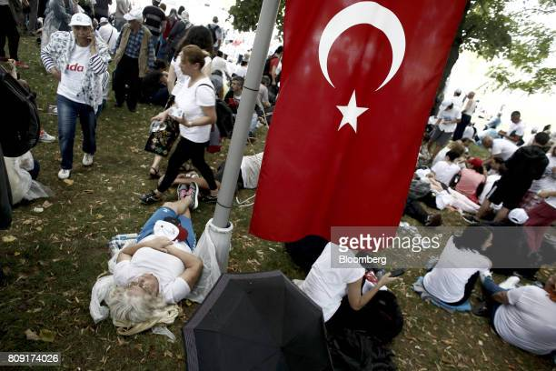 Demonstrators rest under a Turkish national flag during a break in the 20th day of a 425kilometer march in Kocaeli Turkey on Tuesday July 4 2017...
