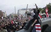 Demonstrators ride on top a 1950sera armoured car they commandeered during violent street protests on October 23 2006 in Budapest Hungary The country...