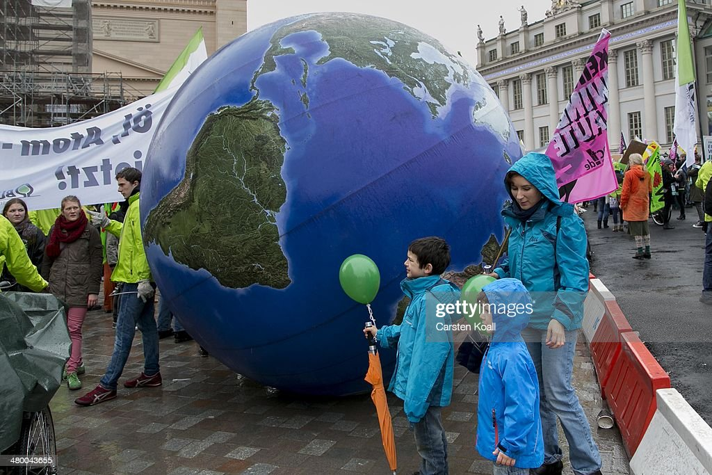 Demonstrators rolling a model of the globe while Demonstrators march to demand a faster transition to renewable energy sources on March 22, 2014 in Postdam, Germany. Similar protests are being held across Germany today as Germany's drive toward covering a higher portion of its energy demands with renewables has faltered recently due to high costs and an incomplete infrastructure.