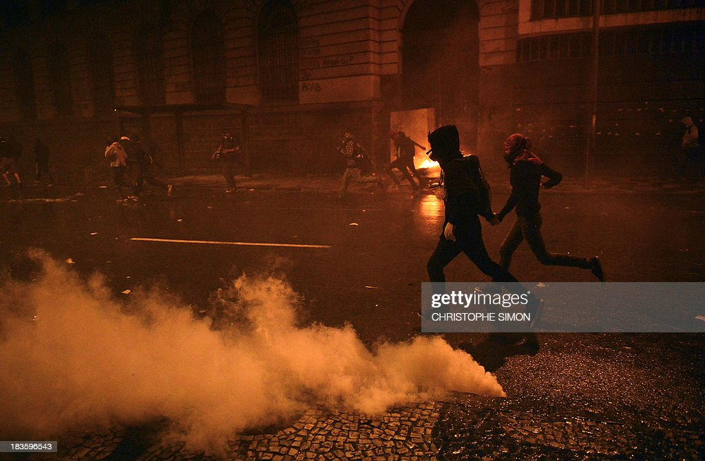 Demonstrators run amid tear gas bombs shot by riot police following clashes, after a peaceful teachers protest demanding better working conditions and against police beating, on October 7, 2013 in Rio de Janeiro. AFP PHOTO / CHRISTOPHE SIMON