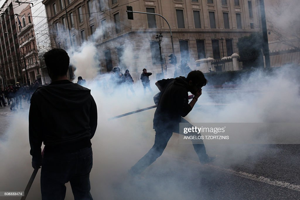 TOPSHOT - Demonstrators run among tear gas during a massive protest in front of the Greek parliament in Athens on February 4, 2016. Thousands of people marched across Greece on February 4, 2016 as diverse classes united in a crippling general strike over a pension overhaul that has sparked a major backlash against embattled leftist Prime Minister Alexis Tsipras. / AFP / ANGELOS
