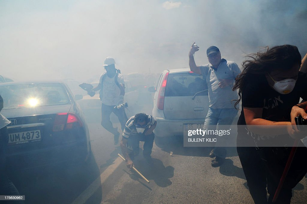 Demonstrators run away from tear gas during clashes between Turkish police and protestors on August 5, 2013, as police and gendarmerie block the way to a courthouse in Silivri, near Istanbul, where prosecutors are scheduled to deliver their final arguments in the case against 275 people accused of plotting to overturn the Islamic-leaning government. Among the defendants in the high-profile case -- seen as a key test in Prime Minister Recep Tayyip Erdogan's showdown with secularist and military opponents -- are ex-military chief Ilker Basbug and other army officers as well as lawyers, academics and journalists.