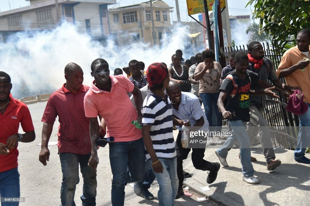 Demonstrators run for cover as Haitian police fire tear gas to disperse an anti-government protest in the centre of the Haitian capital Port-au-Prince, on September 12, 2017. Demonstrators took to the streets to protest against the government and the new budget for 2017-2018, throwing stones at the police, setting tires on fire and blocking some streets. /