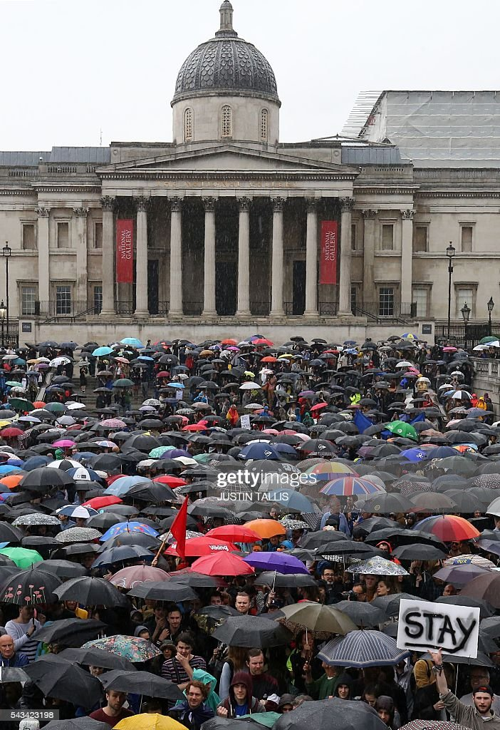 Demonstrators shelter under umbrellas at an anti-Brexit protest in front of the National gallery in Trafalgar Square in central London on June 28, 2016. EU leaders attempted to rescue the European project and Prime Minister David Cameron sought to calm fears over Britain's vote to leave the bloc as ratings agencies downgraded the country. Britain has been pitched into uncertainty by the June 23 referendum result, with Cameron announcing his resignation, the economy facing a string of shocks and Scotland making a fresh threat to break away. / AFP / JUSTIN