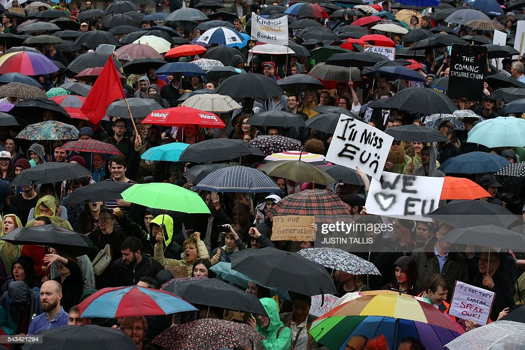 Demonstrators shelter under umbrellas at an anti-Brexit protest in Trafalgar Square in central London on June 28, 2016. EU leaders attempted to rescue the European project and Prime Minister David Cameron sought to calm fears over Britain's vote to leave the bloc as ratings agencies downgraded the country. Britain has been pitched into uncertainty by the June 23 referendum result, with Cameron announcing his resignation, the economy facing a string of shocks and Scotland making a fresh threat to break away. / AFP / JUSTIN