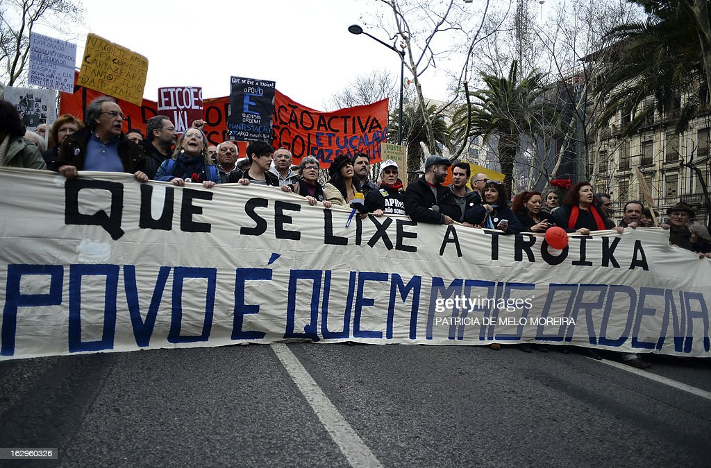Demonstrators shout slogans and carry a banner reading 'Damn Troika - The power lies to the people' as they march through downtown Lisbon on March 2, 2013. Several thousands of people demonstrate today in the Portuguese capital to protest against government austerity measures.
