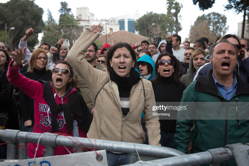 Demonstrators shout slogans and gesture during a protest outside the Cypriot parliament in Nicosia, Cyprus, on Friday, March 22, 2013. The aid package Cyprus is seeking would only provide temporary relief as it risks triggering a capital flight that would push the nation closer to needing to restructure its debts. Photographer: Simon Dawson/Bloomberg via Getty Images