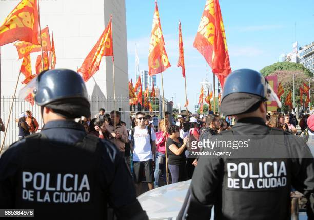 Demonstrators shout slogans and hold banners as policemen take security measures in the city street during the national CGT strike and the CTA...