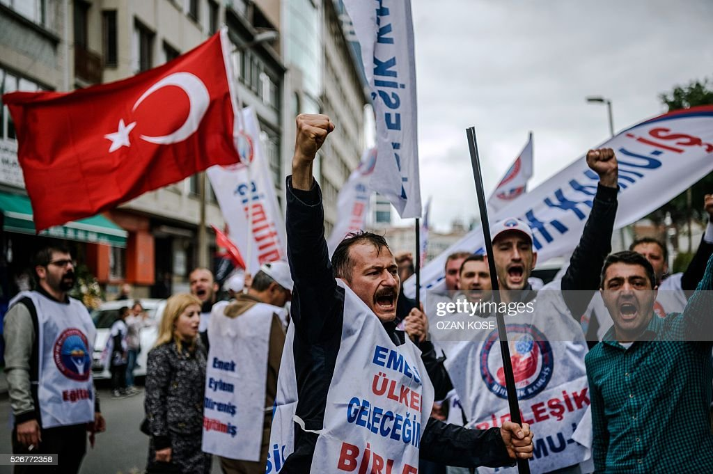 Demonstrators shout slogans and hold up their fists during a May Day rally in Sisli, a district of Istanbul, on May 1, 2016. Turkish labour activists and leftists marked the annual May Day holiday, with thousands of security deployed and bracing for trouble after the authorities refused to allow protests in central Taksim Square. / AFP / OZAN