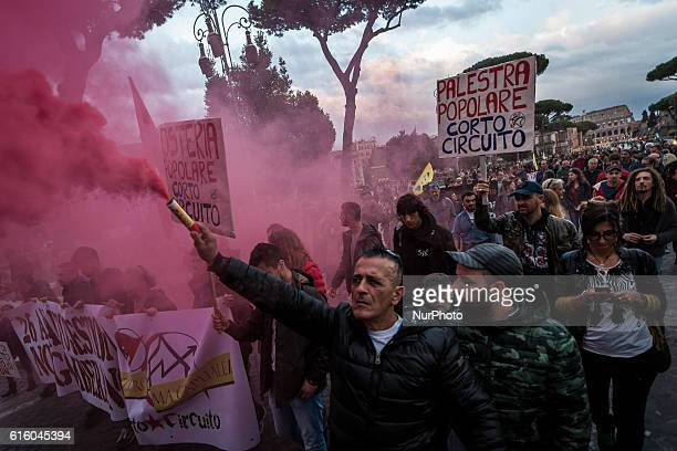 Demonstrators shout slogans and march with lit flares and flags as they take a rally to protest against the eviction of CSOA Corto Circuito Social...