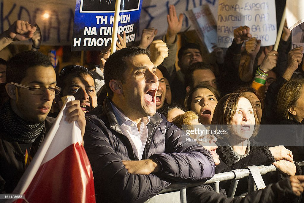 Demonstrators shout slogans and waves banners during a protest outside the parliament against bank deposit tax plans in Nicosia, Cyprus, on Tuesday, March 19, 2013. Euro-area finance ministers told Cyprus to raise 5.8 billion euros ($7.5 billion) from bank depositors to unlock emergency loans, maintaining the revenue target while suggesting sparing small-scale savers. Photographer: Simon Dawson/Bloomberg via Getty Images