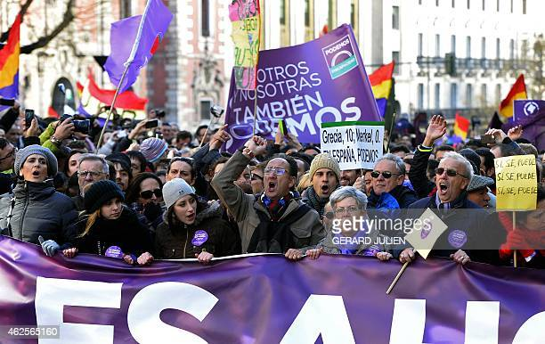 Demonstrators shout slogans as they hold flags placards and a banner during the 'March for Change' planned by leftwing party Podemos that emerged out...