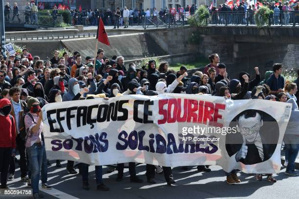 Demonstrators shout slogans as they march with a banner depicting French President and reading let's erace that smile' during a rally in Rennes on...