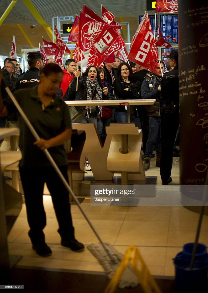 Demonstrators shout slogans in front of a McDonalds restaurant, forcing it to close for business, while a cleaning lady cleans the floor at Barajas airport on November 14, 2012 in Madrid, Spain. A coordinated general strike by unions in Spain and Portugal has paralysed public transport in the two countries with further strikes planned across Europe. The strike against the governments' austerity measures have force hundreds of flights to be cancelled and factories and ports to come to a standstill.